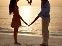 foto pareja formando un corazon en la playa