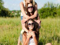 três-namoradas-felizes-das-jovens-mulheres-que-abraçam-contra-o-céu-azul-35906366