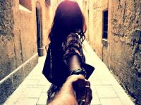 mujer en un callejon de la mano